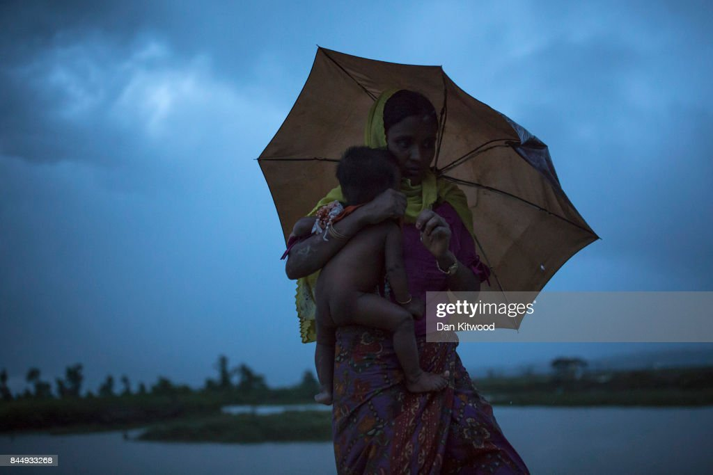 Rohingya refugees walk across Paddy fields in the pouring rain at dusk after crossing the border from Myanmar on September 09, 2017 in Gundum, Bangladesh. Recent reports have suggested that around 290,000 Rohingya have now fled Myanmar. Those who left have spoken of violence erupting in Rakhine state, when the country's security forces allegedly launched an operation against the Rohingya Muslim community.