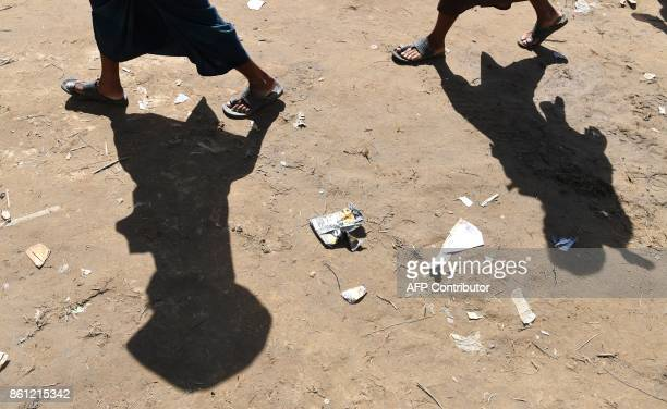 Rohingya refugees walk back after collecting health and sanitation aid at the Balukhali refugee camp in the Bangladeshi district of Ukhia on October...
