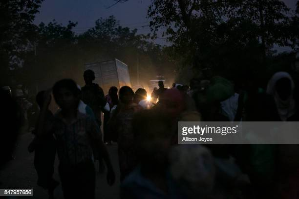 Rohingya refugees walk down a road on September 16 2017 in Cox's Bazar Bangladesh Nearly 400000 Rohingya refugees have fled into Bangladesh since...