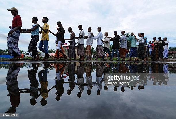 Rohingya refugees walk near their shelters in Bayeun Village Aceh Province Indonesia on May 25 2015 Indonesia has begun search and rescue operations...