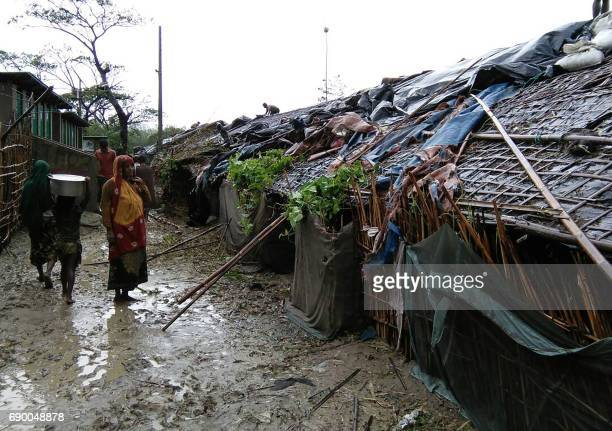 Rohingya refugees walk next to huts in a makeshift camp in Bangladesh's Cox's Bazar district on May 30 2017 after Cyclone Mora made landfall in the...