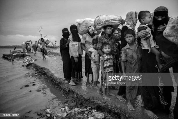 COX'S BAZAR BANGLADESH SEPTEMBER 19 Rohingya refugees walk on a road after arriving on the Bangladesh side of the Naf River at Shah Porir Dwip after...