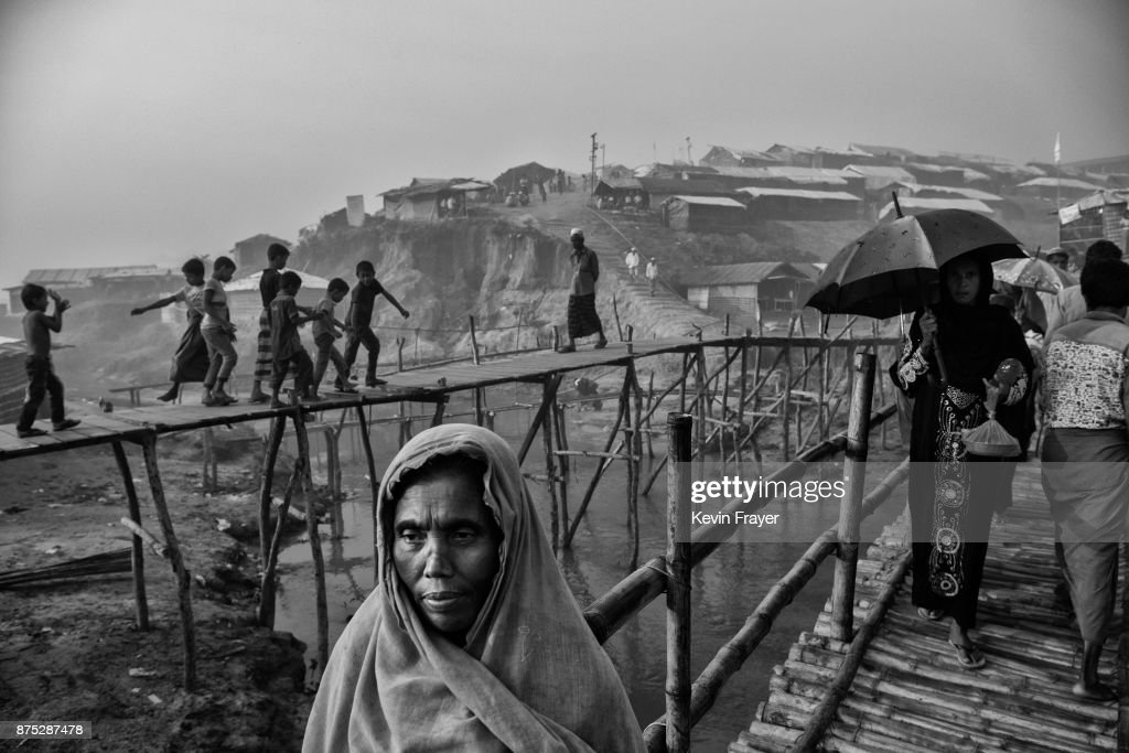COX'S BAZAR, BANGLADESH - OCTOBER 27: Rohingya refugees walk on makeshift bamboo bridges on October 27, 2017 at the Kutupalong refugee camp near Cox's Bazar, Bangladesh. More than 600,000 Rohingya refugees have flooded into Bangladesh to flee an offensive by Myanmar's military that the United Nations has called 'a textbook example of ethnic cleansing'. The refugee population continues to swell further, with thousands more Rohingya Muslims making the perilous journey on foot toward the border, or paying smugglers to take them across by water in wooden boats. Hundreds are known to have died trying to escape, and survivors arrive with horrifying accounts of villages burned, women raped, and scores killed in the 'clearance operations' by Myanmar's army and Buddhist mobs that were sparked by militant attacks on security posts in Rakhine state on August 25, 2017. What the Rohingya refugees flee to is a different kind of suffering in sprawling makeshift camps rife with fears of malnutrition, cholera, and other diseases. Aid organizations are struggling to keep pace with the scale of need and the staggering number of them - an estimated 60 percent - who are children arriving alone. Bangladesh, whose acceptance of the refugees has been praised by humanitarian officials for saving lives, has urged the creation of an internationally-recognized 'safe zone' where refugees can return, though Rohingya Muslims have long been persecuted in predominantly Buddhist Myanmar. World leaders are still debating how to confront the country and its de facto leader, Aung San Suu Kyi, a Nobel Peace Prize laureate who championed democracy, but now appears unable or unwilling to stop the army's brutal crackdown. During a recent visit to Myanmar, U.S Secretary of State Rex Tillerson called for a 'credible' probe into human rights violations against the Rohingya but said he would advise against full sanctions on the country.