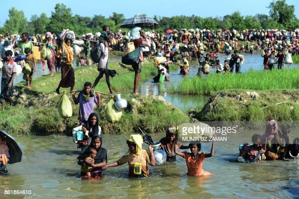 TOPSHOT Rohingya refugees walk through a shallow canal after crossing the Naf River as they flee violence in Myanmar to reach Bangladesh in...