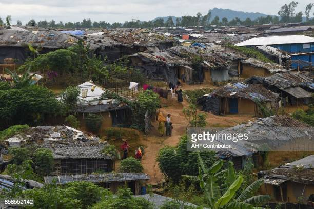 Rohingya refugees walk through the Kutupalong refugee camp in Bangladesh's Ukhia district on October 7 2017 Rohingya militants whose attacks...