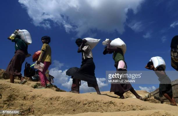 TOPSHOT Rohingya refugees walk with relief materials at Thankhali refugee camp in Bangladesh's Ukhia district on November 14 2017 More than 600000...