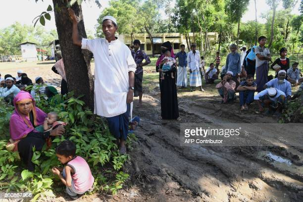 Rohingya refugees who were detained while attempting to sneak out of their camps towards the city wait at a field at Ukhia on October 13 2017...