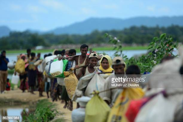 Rohingya refugees who were stranded walk near the no man's land area between Bangladesh and Myanmar in the Palongkhali area next to Ukhia on October...