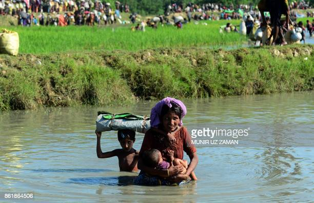 Rohingya woman carries a child as they cross a shallow canal after crossing the Naf River as they flee violence in Myanmar to reach Bangladesh in...
