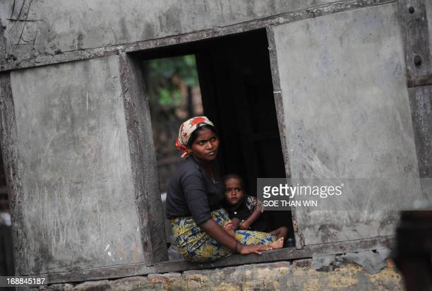 A Rohingya woman holds her child as she looks out from window at a temporary relief camp in a school in Thetkaepyin village on the outskirts of...