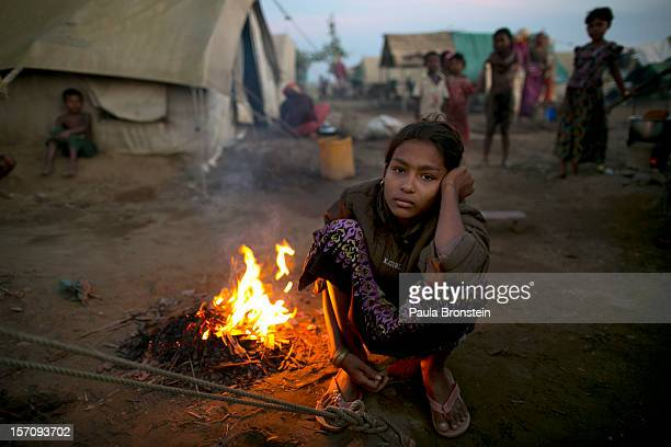 Rohingya woman sits by a fire at a crowded internally displaced persons camp November 23 2012 on the outskirts of Sittwe Myanmar An estimated 111000...