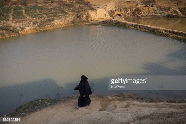 A Rohingya woman walks beside the waterbody at Kutupalong Refugee Camp Cox's Bazar Bangladesh on February 13 2017 After attacks by Rohingya militants...