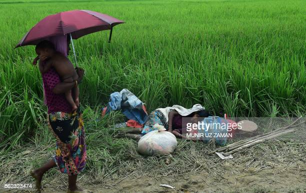 A Rohingya woman with a baby walks past a sick refugee resting in an area near no man's land on the Bangladesh side of the border with Myanmar after...