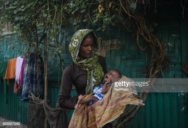 A Rohingya women carrying her child in front of the makeshift Leda Rohingya refugee camp on February 15 2017 in Bangladesh Thousands of Rohingya...