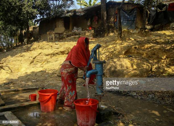 A Rohingya women collecting water from a water pump oustide her makeshift refugees camp in Kutupalong Bangladesh on February 15 2017 Almost 60000...