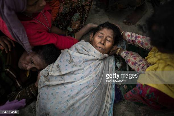 Rohingya women comfort two elderly women after the wooden boat they were travelling on from Myanmar crashed into the shore and tipped everyone out on...