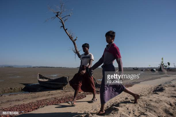 TOPSHOT Rohingyas walk towards a registration point after arriving the night before from Myanmar near Shah Barir Dip at Cox's Bazar on December 3...