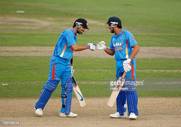 Rohit Sharma and Virat Kohli of India bump fists during the one day tour match between Sussex and India at The County Ground on August 25 2011 in...