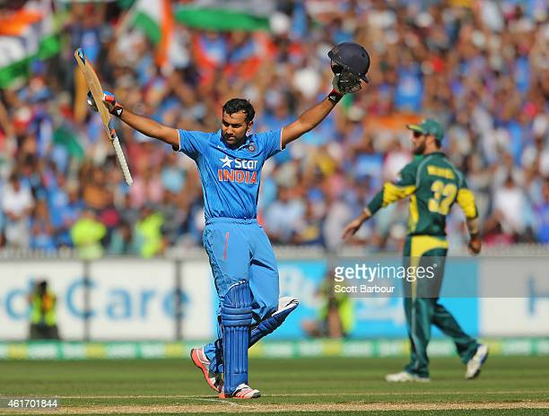 Rohit Sharma of India celebrates as he reaches his century as Glenn Maxwell of Australia looks on during the One Day International match between...