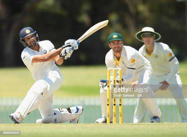 Rohit Sharma of India hits a six as wicketkeeper Seb Gotch of the Cricket Australia XI looks on during the international tour match between the...