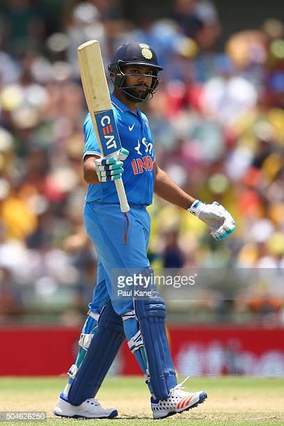 Rohit Sharma of India raises his bat to celebrate his half century during the Victoria Bitter One Day International Series match between Australia...