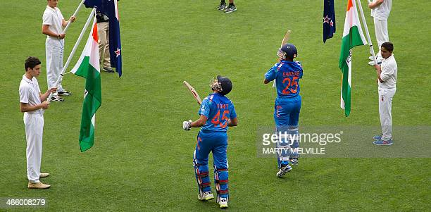 Rohit Sharma with teammate Shikhar Dhawan of India walk onto the field at the beginning of India's inningsduring the fifth and final international...