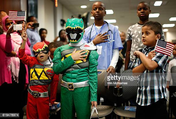 Rojan Pandey and Yusef Mousa Aryouib dressed as Power Rangers place their hands over their heart as they recite the Oath of Allegiance during a...
