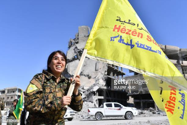 Rojda Felat a Syrian Democratic Forces commander walks with her group's flag at the iconic AlNaim square in Raqa on October 17 2017 USbacked forces...