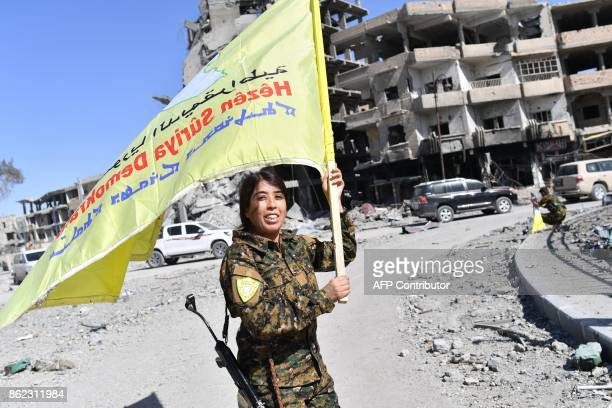 TOPSHOT Rojda Felat a Syrian Democratic Forces commander waves her group's flag at the iconic AlNaim square in Raqa on October 17 2017 USbacked...