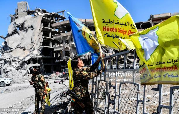 Rojda Felat a Syrian Democratic Forces commander waves her group's flag at the iconic AlNaim square in Raqa on October 17 2017 USbacked forces said...