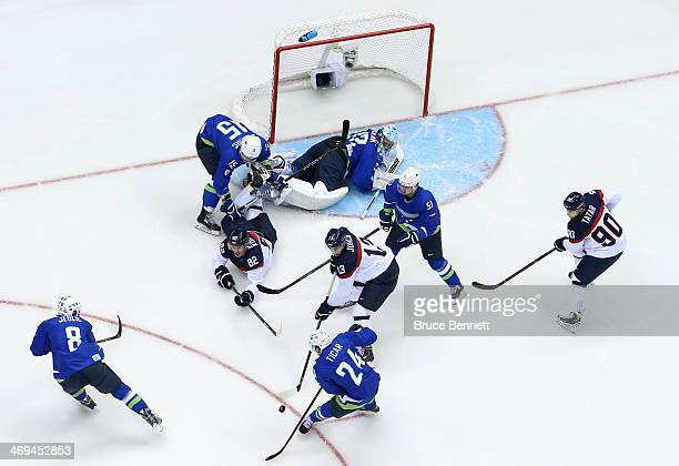 Rok Ticar of Slovenia tries to clear the puck against Tomas Kopecky and Tomas Jurco of Slovakia in the first period during the Men's Ice Hockey...