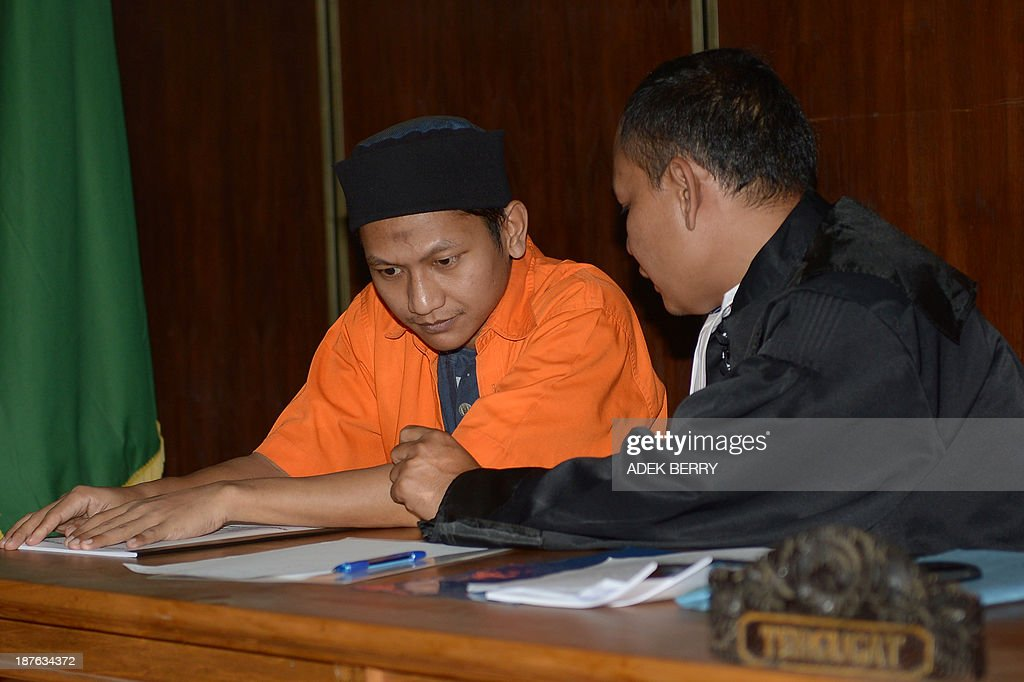 Rokhadi (L) sits next to his lawyer Willy Gustam (R) during his trial at the South Jakarta court in Jakarta on November 11, 2013. Two suspected Indonesian extremists went on trial on November 11 accused over an 'evil conspiracy' to bomb the Myanmar embassy to avenge the killing of Rohingya Muslims in their country.