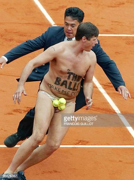 A Roland Garros employee catches a naked spectator who interrupted the Roland Garros French Tennis Open final match between Netherlands' Martin...