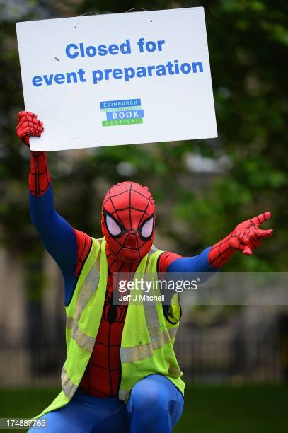Roland Gulliver associate director of the Edinburgh International Book Festival dressed in costume as comic strip character Spiderman helps to put...