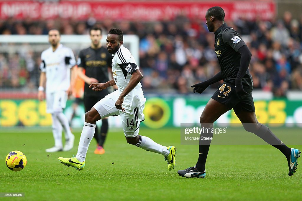 Roland Lamah (L) of Swansea City is tracked by <a gi-track='captionPersonalityLinkClicked' href=/galleries/search?phrase=Yaya+Toure&family=editorial&specificpeople=550817 ng-click='$event.stopPropagation()'>Yaya Toure</a> (R) of Manchester City during the Barclays Premier League match between Swansea City and Manchester City at the Liberty Stadium on January 1, 2014 in Swansea, Wales.