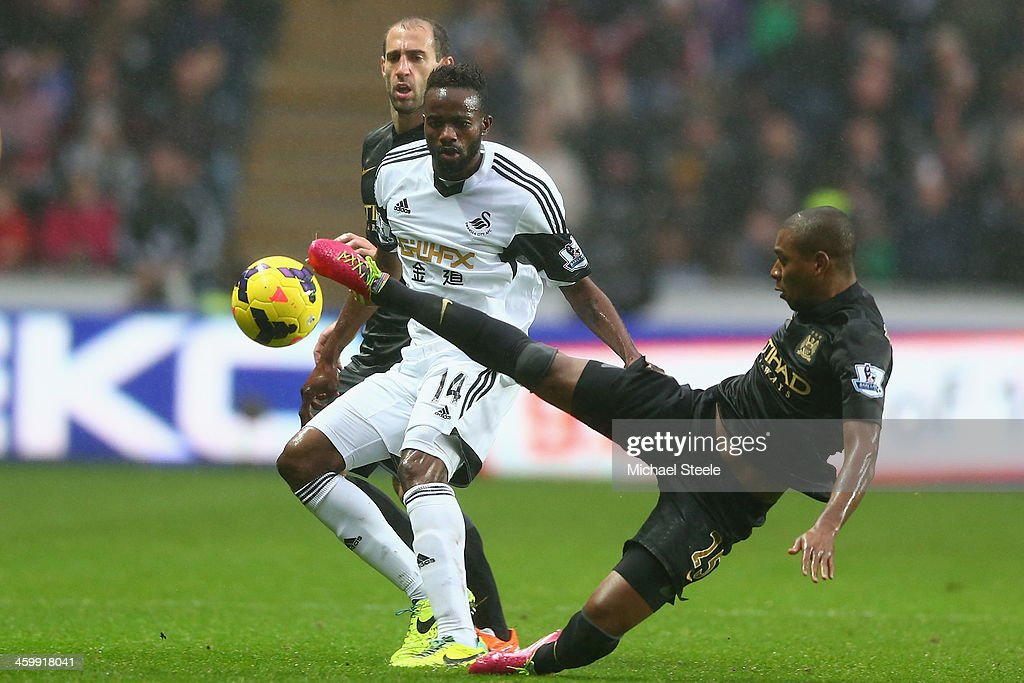 Roland Lamah (L) of Swansea City watches <a gi-track='captionPersonalityLinkClicked' href=/galleries/search?phrase=Fernandinho+-+Soccer+Player+-+Manchester+City&family=editorial&specificpeople=10093285 ng-click='$event.stopPropagation()'>Fernandinho</a> (R) of Manchester City during the Barclays Premier League match between Swansea City and Manchester City at the Liberty Stadium on January 1, 2014 in Swansea, Wales.
