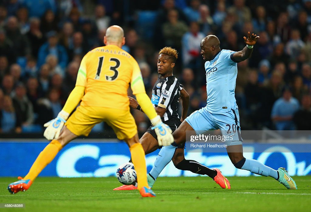 Rolando Aarons of Newcastle United scores the opening goal under pressure from Eliaquim Mangala of Manchester City during the Capital One Cup Fourth Round match between Manchester City and Newcastle United at Etihad Stadium on October 29, 2014 in Manchester, England.