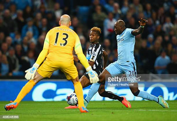 Rolando Aarons of Newcastle United scores the opening goal under pressure from Eliaquim Mangala of Manchester City during the Capital One Cup Fourth...