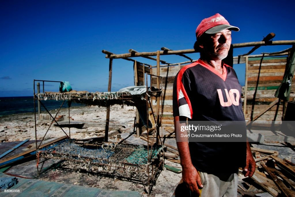 Rolando Hung Batista stands amid the ruins of his house near his efforts to rebuild a wooden shelter after Hurricane Ike tore through a week earlier...