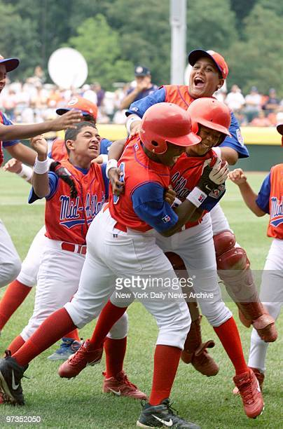 Rolando Paulino AllStars' players leap on teammate Carlos Garcia after Garcia hit a grand slam home run in the first inning of game against the...