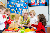 Nursery teacher playing kitchen roleplay with her students in the classroom.