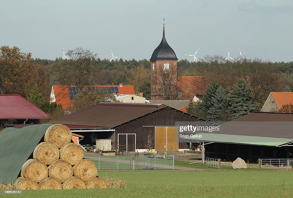Roles of hay stand stacked as the village church stands behind on October 31, 2013 in Atterwasch, Germany. According to plans by Swedish energy conglomerate Vattenfall and approved by the Brandenburg state legislature, Atterwasch and at least four other communities are to be raized and their inhabitants compensated and relocated in order to make way for the expansion of a nearby open-pit lignite coal mine. Energy policy and the role of coal is a heated topic at the moment in coalition negotiations between the Social Democrats (SPD) and Christian Democrats (CDU) currently taking place in Berlin.