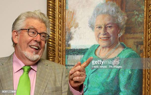 Rolf Harris poses next to his portrait of Queen Elizabeth II as he celebrates 65 years in art as he opens his A Life in Art' exhibition at the...