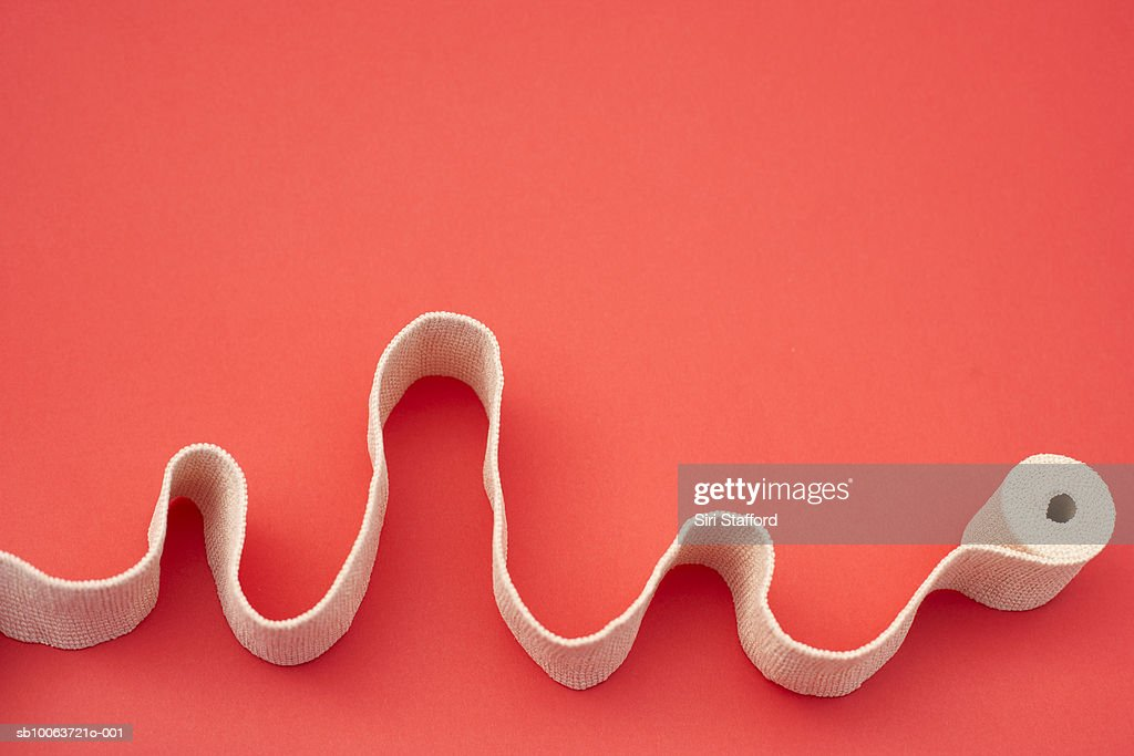 Roll of athletic tape on red background, high angle view