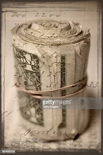 A roll of dollar bills with a handwritten note overlayed