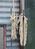Roll up nylon rope and knot against zinc wall.
