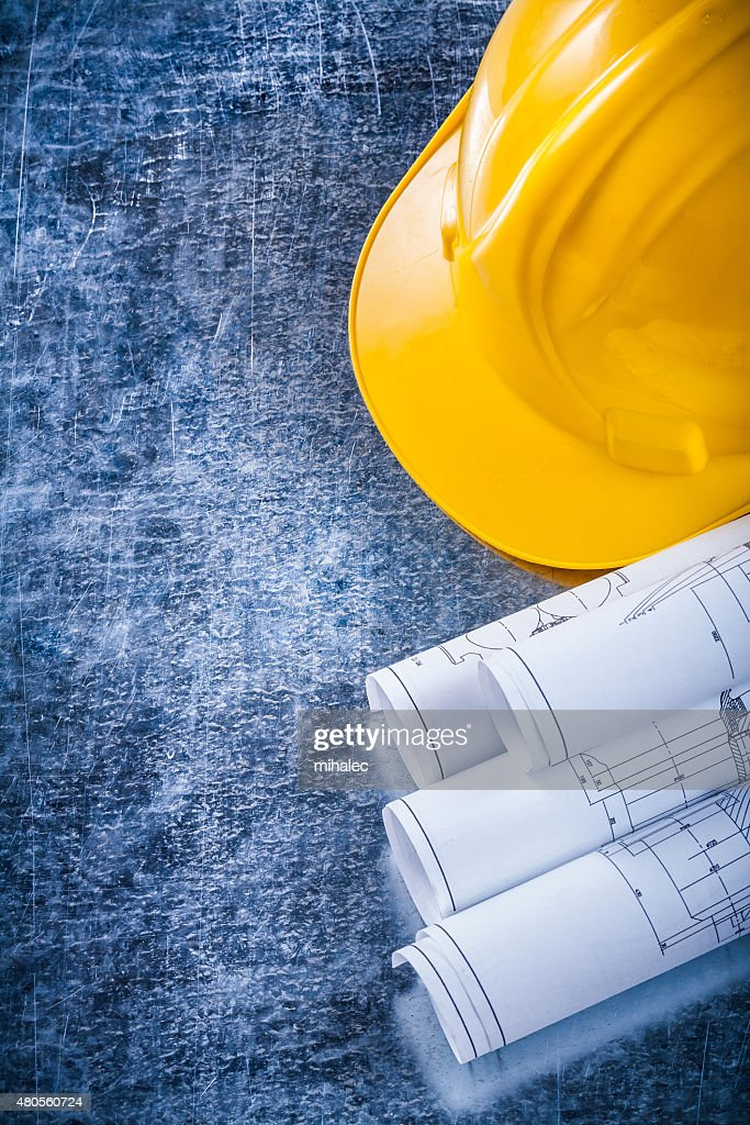 Rolled construction plans and yellow hard hat on metallic scratc : Stock Photo
