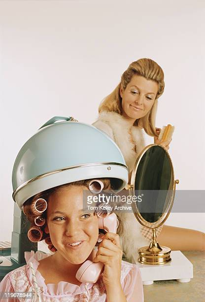 Rolled hair of teenage girl under hair steamer, mother in background