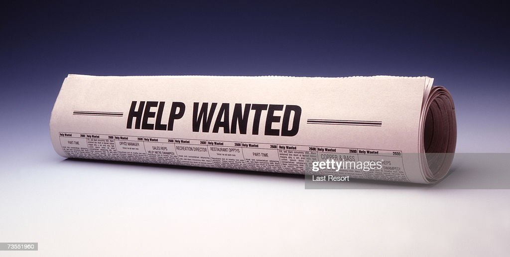 Rolled newspaper titled help wanted, close-up : Stock Photo