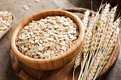Rolled oats or oat flakes and golden wheat ears on wooden background. Concept of agriculture, healthy eating, healthy lifestyle